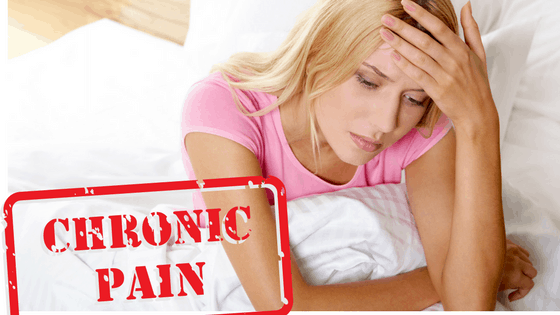 Woman sitting bed holding her head with graphic stamp saying Chronic Pain