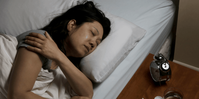Woman lying in a bed with a nightstand and alarm clock visible