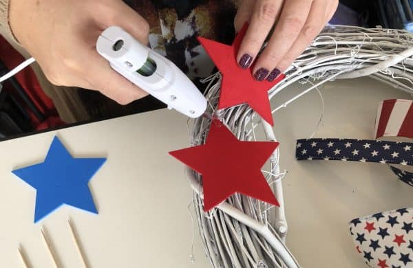 Gluing wooden stars to a grapevine wreath
