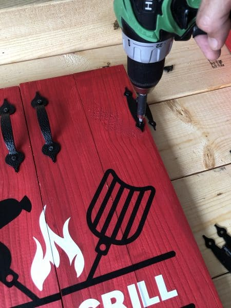 Drill attaching hinges to wooden doors for grill tools organizer
