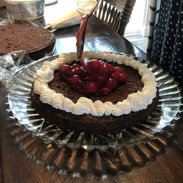 Putting cherry filling on a german chocolate cake